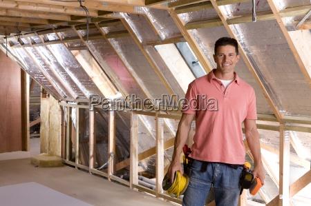 laechelnd elektriker stehend im dachboden im