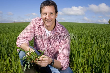 smiling farmer crouching in field and