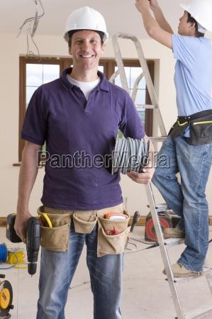 laechelnd elektriker halten kabelspule und bohren