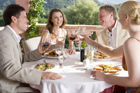 well dressed couples toasting wine glasses