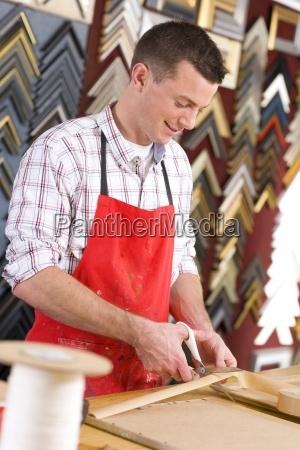 craftsman working on frame in frame