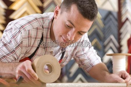 handwerker arbeiten auf rahmen in rahmengeschaeft