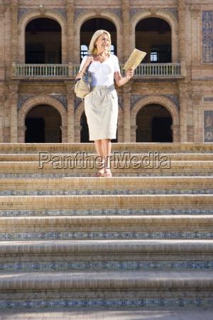 seniorin mit touristischer karte absteigende stufen