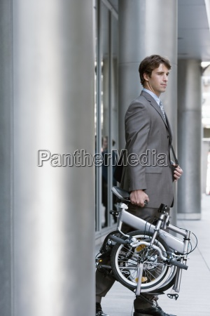 businessman leaving office building carrying folding