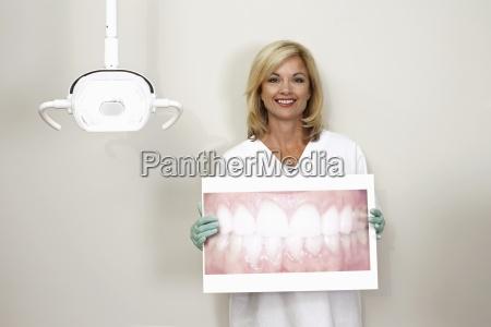 female dentist standing in dental surgery