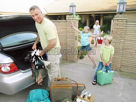 vater laden kofferraum mit gepaeck familie