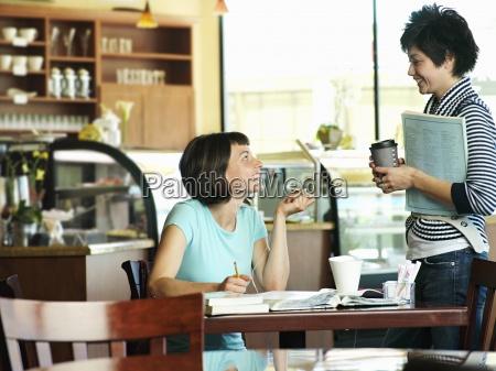 two women talking in cafe woman