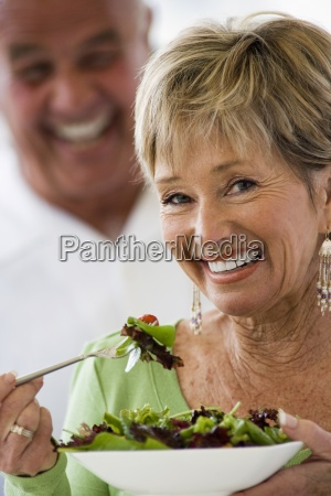 senior woman eating fresh salad man