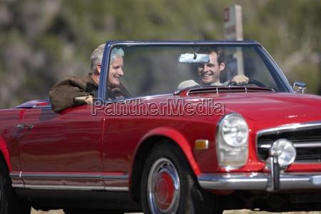 zwei maenner im roten cabrio auto