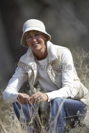 woman sitting outdoors wearing bucket hat