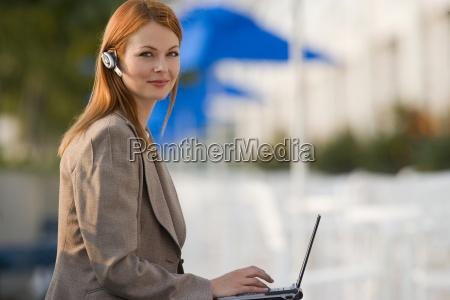 geschaeftsfrau mit handy freisprecheinrichtung mit laptop
