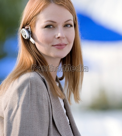 businesswoman wearing mobile phone hands free