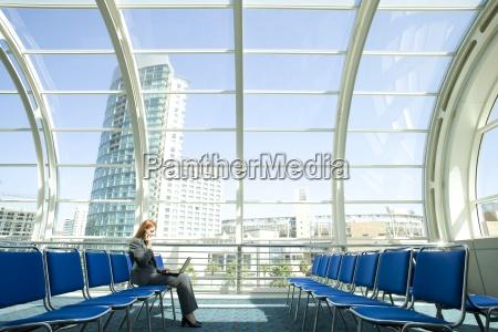geschaeftsfrau warten in flughafen abflughalle mit