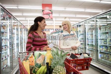 zwei frauen die im supermarkt kaufen