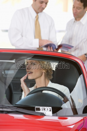 woman sitting in red convertible in