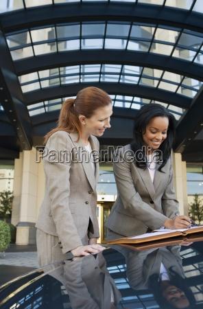 zwei geschaeftsfrauen vor dem hotel stehen