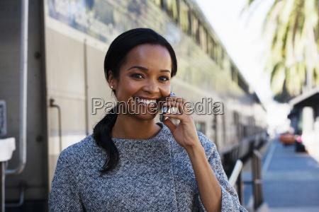businesswoman standing on railway platform beside