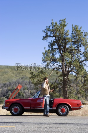 man standing beside red convertible car