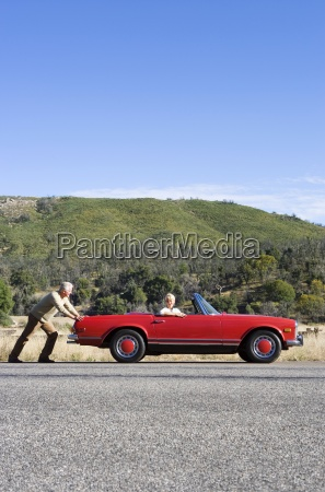 senior couple experiencing car trouble on
