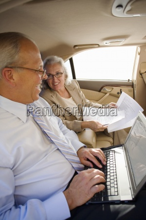 businessman and woman sitting in back