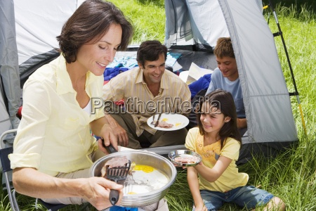 family eating fried breakfast on camping