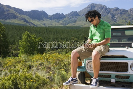 young man sitting on bonnet of