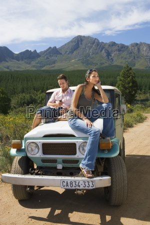 young couple sitting on bonnet of