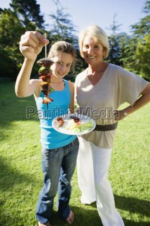 senior woman standing beside granddaughter 11
