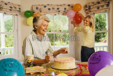 senior woman and adult daughter preparing