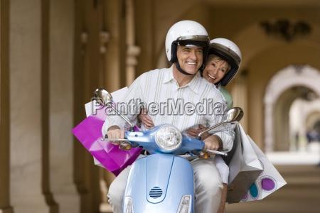 senior couple riding on motor scooter