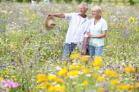 smiling senior couple looking at blossoms