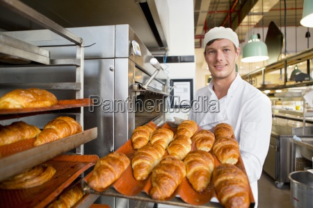 smiling baker holding tray of bread