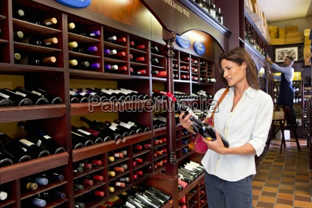 curious woman examining bottles in wine