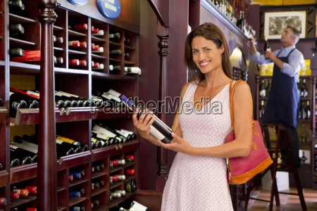 smiling woman holding bottle in wine