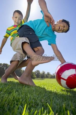 laechelnden jungen spielen fussball im park