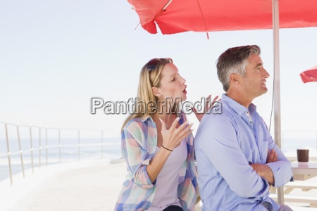 couple arguing under umbrella at waterfront