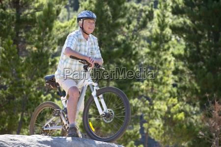 aeltere menschen mountainbike im wald reiten