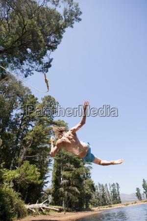 man jumping into rural lake