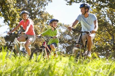 family riding mountain bikes in rural