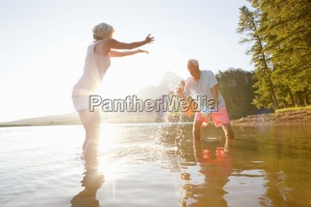 older couple splashing each other in