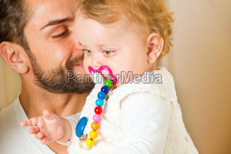 vater mit kind auf dem arm
