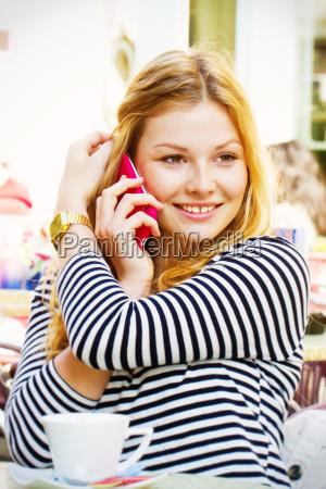 junger frau im cafe beim telefonieren