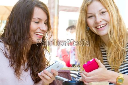zwei freundinnen mit handy im cafe