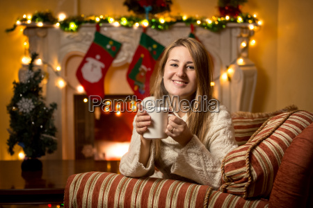 woman sitting at fireplace with cup