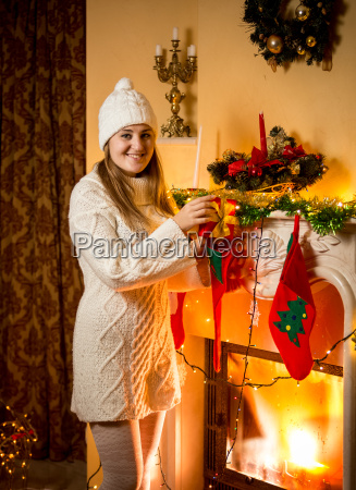 woman in sweater holding red gift