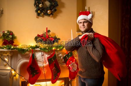smiling man carrying big santa bag