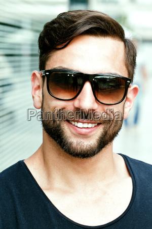 junger attraktiver mann mit sonnenbrille