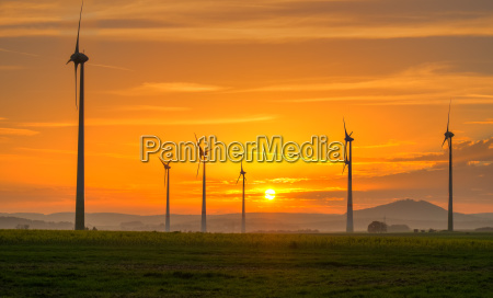 sunset and wind turbines in germany