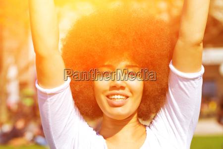 glueckliche junge frau mit afrofrisur in
