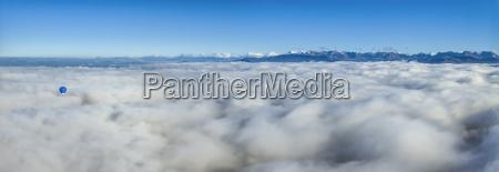 heissluftballon auf wolken zu sehen alpen